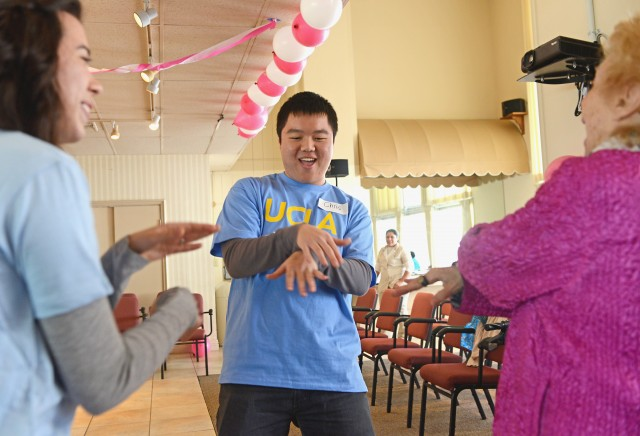 First-year business economics student Christopher Tang dances with a resident at Vintage Westwood Horizons for a Valentine's Day-themed event organized by the UCLA Volunteer Center on Saturday.