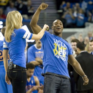 Former football running back Johnathan Franklin, UCLA's career record holder for rushing yards, leads the Pauley Pavilion crowd in an 8-clap during a timeout in Wednesday night's basketball game against USC.