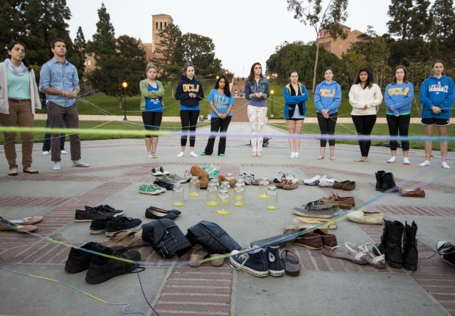 Students stand around a circle of shoes surrounding 11 jars representing the nearly 11 million people killed in the Holocaust. The ceremony, which took place Sunday night, is part of Holocaust Remembrance Day. The event was organized by the student group Bearing Witness.