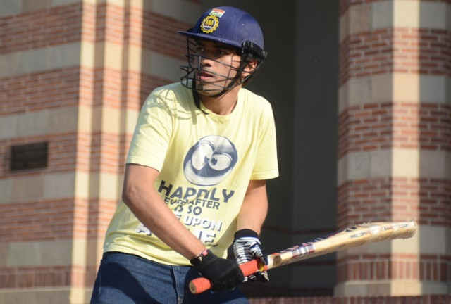 Meet Bhagdev, a second-year computer science student from India, is shown here wearing a helmet and batting pads which are standard for every batsman in cricket. The unofficial club meets up regularly to play the game at the Intramural Field.