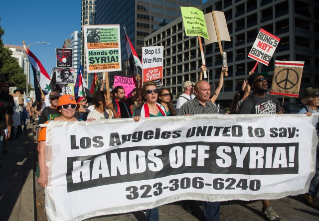 Demonstrators marched on Wilshire Boulevard to protest proposed U.S. airstrikes in Syria.