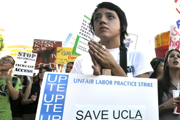 "Holding signs and chanting, ""Whose university? Our university,"" students, faculty and workers congregated in Bruin Plaza Thursday at noon to protest the recent budget cuts, fee increases and faculty furloughs. The protesters gathered as part of a walkout scheduled to take place at all 10 UC campuses."