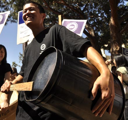 Shinji Sakai, a second-year at UC Riverside, drums on an upside-down tin can at Thursday's walkout. Sakai showed up at UCLA to join student, faculty and worker efforts to protest fee increases, budget cuts and furlough days.
