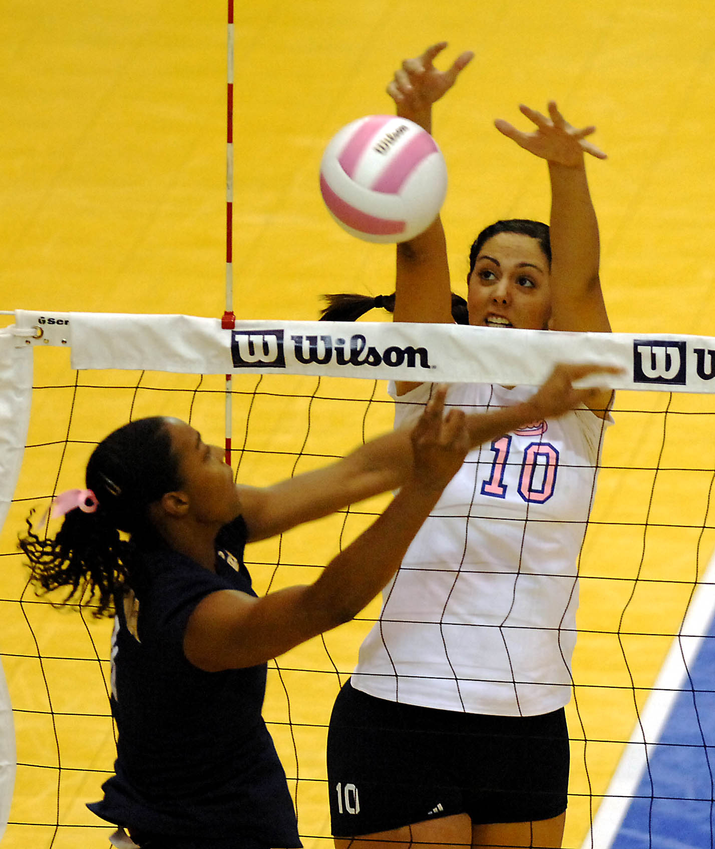 Sophomore middle blocker Amanda Gil blocks against California in a match during last year's Breast Cancer Awareness Week.