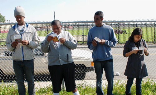 Students at Morningside High School in Inglewood read seed packet directions before planting rows of plants and vegetables at an empty lot across the street from their school as a part of the Empowerment Community Garden project. To vote for this project, go to refresheverything.com