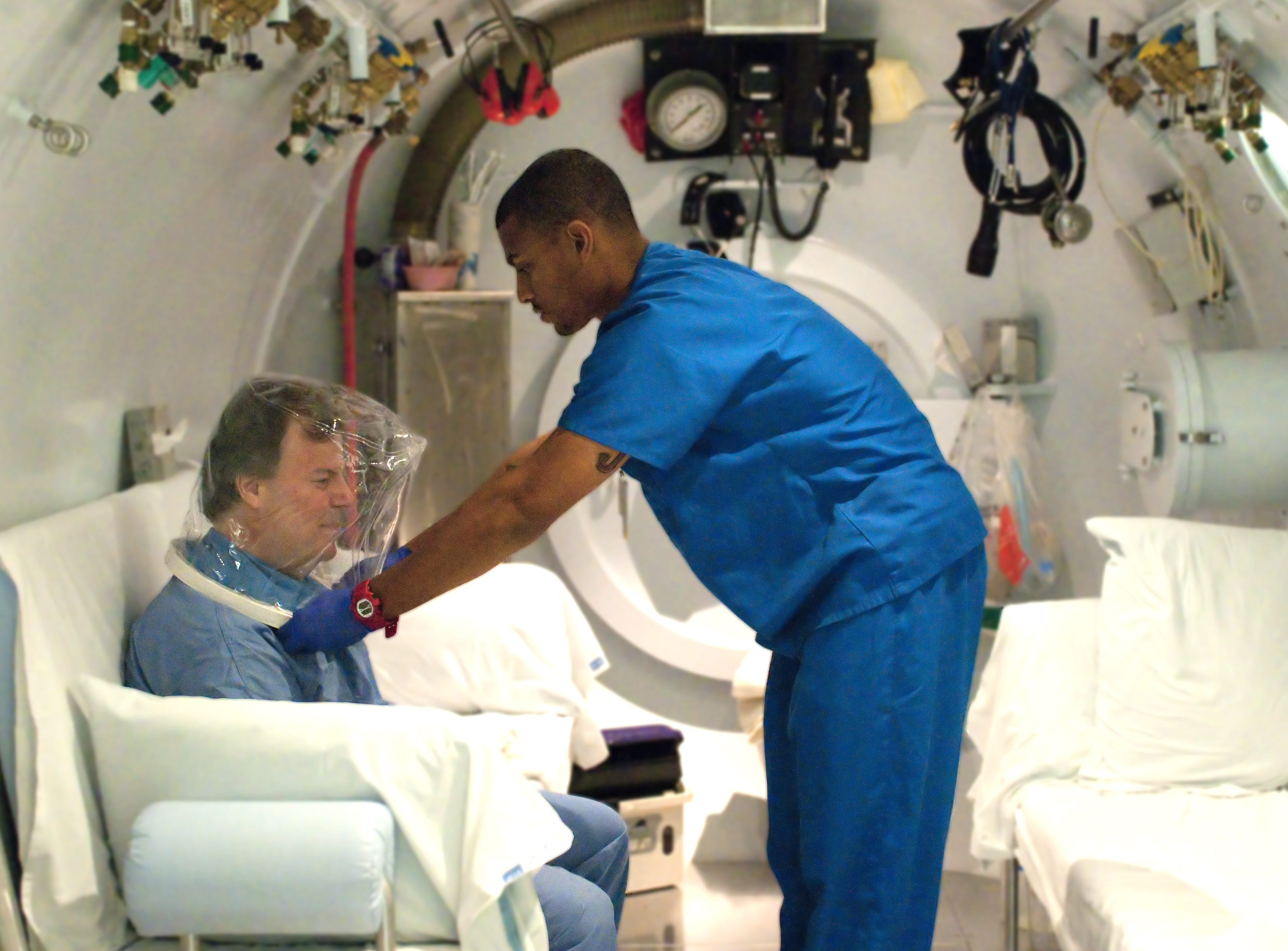 Joey Knox, a technician at the UCLA Gonda Center for Hyperbaric Medicine, puts on an oxygen bubble over patient Jody Glasser, who is currently being treated for damaged blood vessels incurred during radiation therapy for cancer.